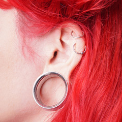 stretched ear lobe piercing with flesh tunnel