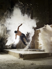 Man jumping in flour dust cloud during freerunning exercise