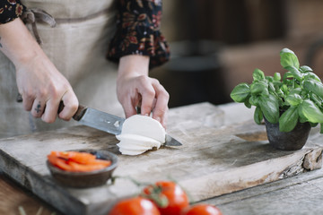 Woman's hands preparing Caprese Salad
