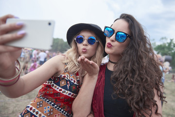 Two young women taking selfie at festival