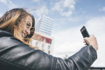 Smiling young woman taking a selfie outdoors
