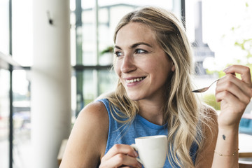 Young woman in cafe drinking coffee