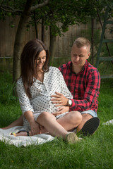 Young pregnant woman and her husband sitting in the garden and watched the movements of the child yet to be born