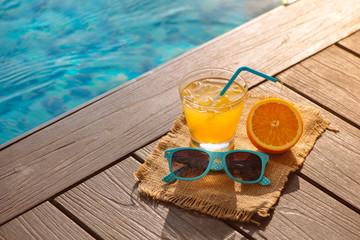 Orange fresh juice smoothie drink, sunglasses near swimming pool