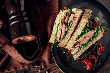 crafted meat sandwich in composition at wooden background