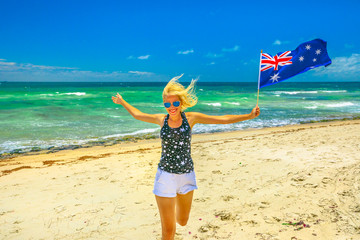 Happy woman running on white beach waving Australian Flag. Blonde tourist enjoying in Mettams Pool, North Beach near Perth in Western Australia. Sunny day, Blue sky. Beach freedom summer holiday.