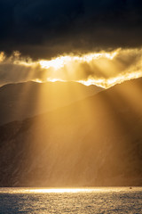 Breathtaking sunbeamsbetween the clouds, mountain and sea