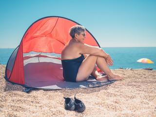 Senior woman relaxing in beach shelter