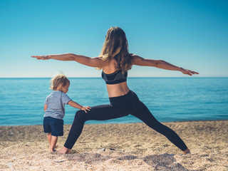 Mother doing yoga with toddler on beach
