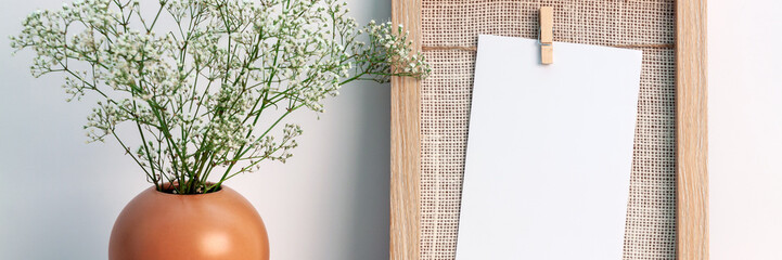 Desk at an empty white wall with a natural wooden frame and a vase with white small flowers