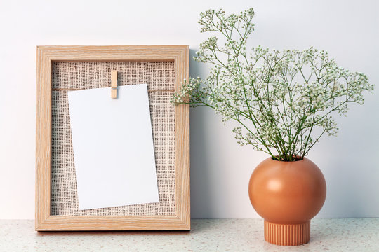 Desk at an empty white wall with a wooden frame with copy space and a vase with white fine flowers