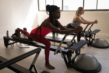 Two women exercising on stretching machine