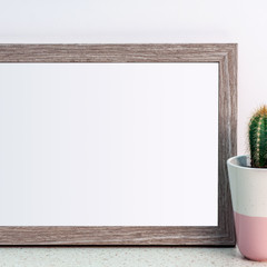 Wooden frame with copy space and cactus in a pink patterned flowerpot on a desk