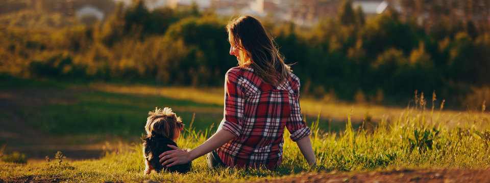 Woman and dog back sitting looking at each other