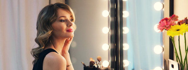 Attractive blonde girl primp at the mirror with lamps in the beauty studio.