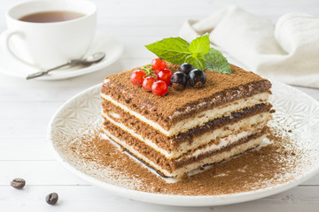 Delicious Tiramisu cake with fresh berries and mint on a plate on a light background. Breakfast...