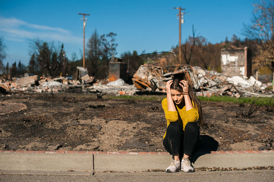 Sad woman home owner holds his head by hand checking burnt out house and yard after fire disaster, consequences of fire disaster accident. Ruins after fire disaster, loss and despair concept.