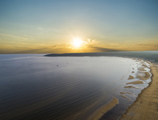 Aerial view of seashore with beach, lagoons and coral reefs. Coastline with sand and water. Tropical landscape. Aerial photography. Birdseye. Sea, beach, sky, clouds.