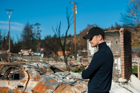 Man owner checking burned and ruined house and yard after fire, consequences of fire disaster accident. Ruins after fire disaster.