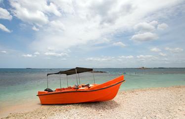Bright orange panga / fishing boat on coral beach in Sri Lanka Asia