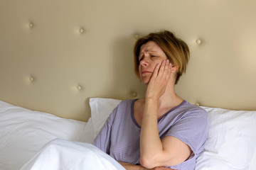 A woman feels sick, sits in bed in the morning. Headache. Toothache.