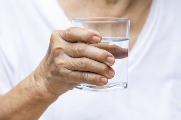 Senior woman's hands drinking polka dot glass of water, Healthy concept
