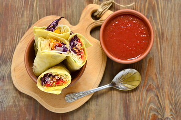 Tortilla wraps with vegetables and tomato sauce, top view