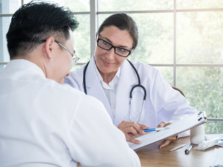 Female doctor in white medical coat with stethoscope giving a consultation to a patient and explaining medical informations.