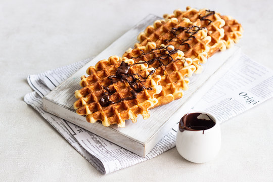Liege style belgian waffles topped with chocolate sauce on a white wooden cutting board