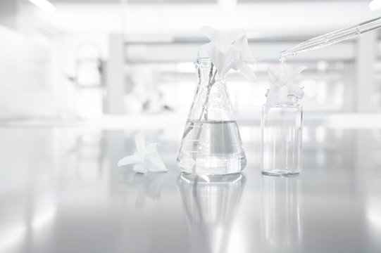 white orchid flower in glass flask with drop of water in research science laboratory background