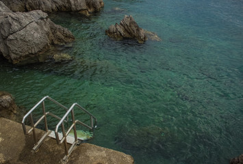 Wall Murals Green coral soft focus swimming place empty environment concept of metal pier with stairs near blue sea waterfront district with water surface small waves and stone rocks