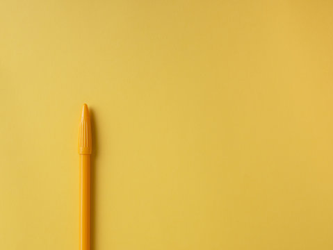 Template with copy space top view close up yellow pen on yellow paper background,  Minimal concept. Flat lay style.