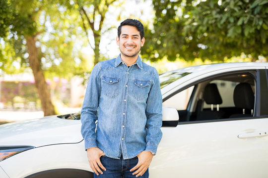 Handsome latin man standing by his car