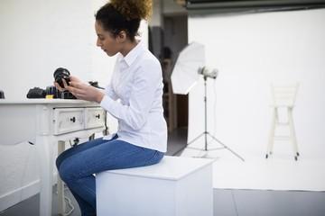 Female photographer checking camera lens