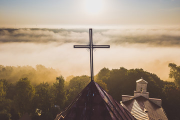Closeup of cross. Aerial view of church in foggy morning
