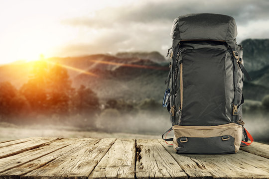Backpack on wooden desk with free space for your decoration and mountains landscape with morning sun light