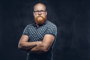 Portrait of a redhead bearded male dressed in a t-shirt posing with crossed arms. Isolated on dark textured background.