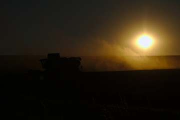 Combine harvester at sunset in the dust of the husks
