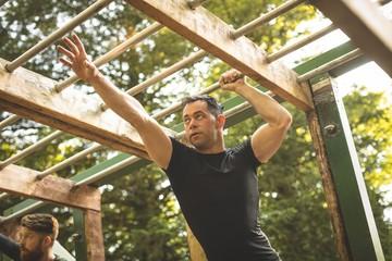 Fit man climbing monkey bars