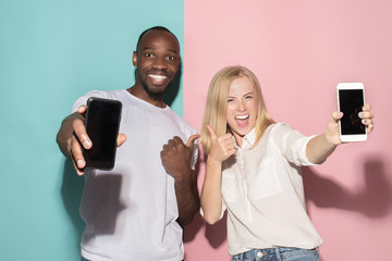 Portrait of a confident casual girl showing blank screen mobile phone and afro man
