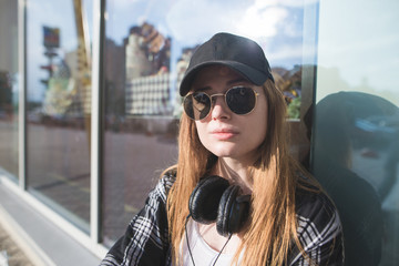 Close portrait of a stylish woman in glasses and a cap on the street looking at the camera. Street style. Portrait of a stylish model