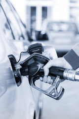 Pumping gas at gas pump. Closeup of man pumping gasoline fuel in car at gas station. Greyscale blue toned image.