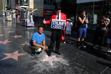A tourist poses for a photo with Greg Donovan, 58, on President Donald Trump's vandalized star on the Hollywood Walk of Fame in Hollywood, Los Angeles