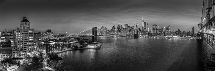 Brooklyn, Brooklyn park, Brooklyn Bridge, Janes Carousel and Lower Manhattan skyline at night seen from Manhattan bridge, New York city, USA. Black and white wide angle panoramic image.