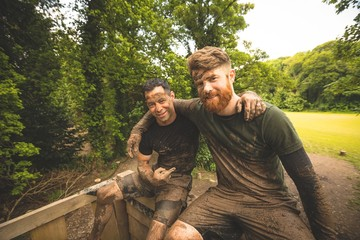 Fit men relaxing over obstacle course