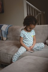 Girl sitting on the sofa and using digital tablet