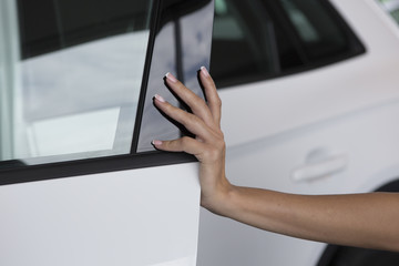 Woman hand on open the new white car door background