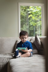 Boy playing on digital tablet while sitting on sofa at home