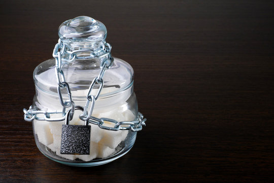glass sugar bowl locked with chain and padlock with copy space