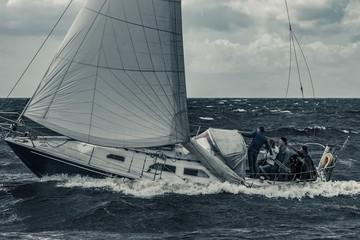 Blue sailboat at storm